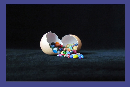 Assorted colorful beads coming out of an egg shell.